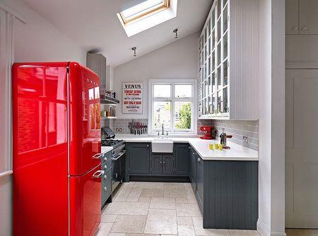 Черная кухонная мебель и красный холодильник